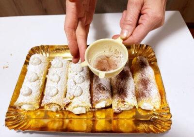 Spolverizzate una parte dei cannoli con il cacao amaro e decorate gli altri con ciuffetti di panna