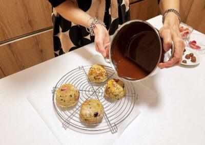 Versate il cioccolato fuso fondente o bianco e caldo sopra gli zuccottini adagiati su una griglia per dolci con sotto un foglio da carta forno