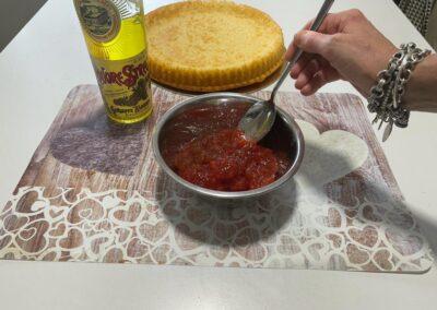 Rovesciate la crostata su un vassoio e aggiungete alla marmellata un cucchiaio scarso di liquore e mescolate
